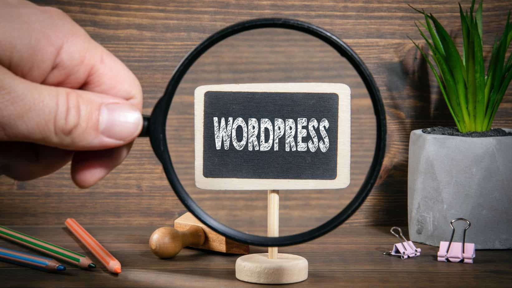 wood background, WordPress on a tablet stand with magnifying glass